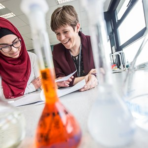 6th Form student smiling with teacher over Science work