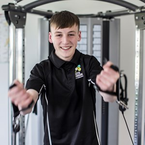 Male student smiling whilst using the gym