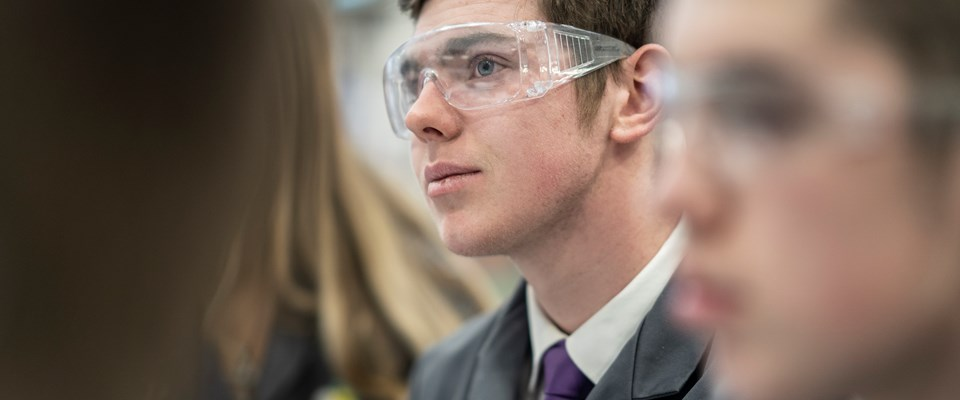 A male student wearing protective goggles smiles during a lesson at UTC South Durham.