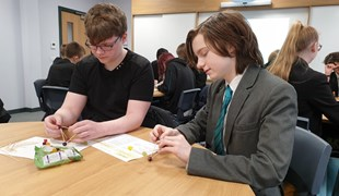 Two students complete a Maths puzzle using cocktail sticks and sweets.