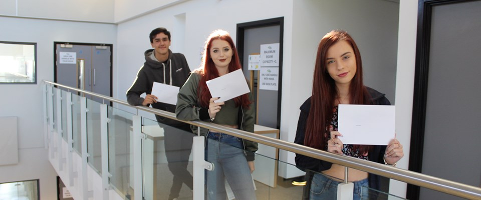 Three students holding their GCSE results at UTC South Durham