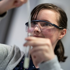 A female student holds up a test tube