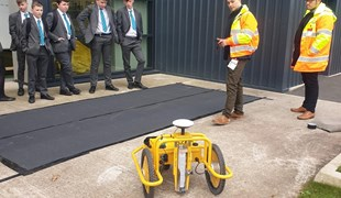 Students watching a line marking robot in operation at careers week