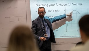 Maths teacher Andy teaching a Maths class. He is seen pointing at a board with a graph displayed.