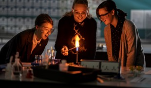 A teacher uses a Bunsen burner for an experiment as two female students look on.