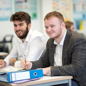Two students wearing business attire smile whilst studying