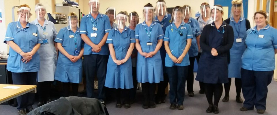 A group of district nurses in blue uniforms wearing the visors made at UTC