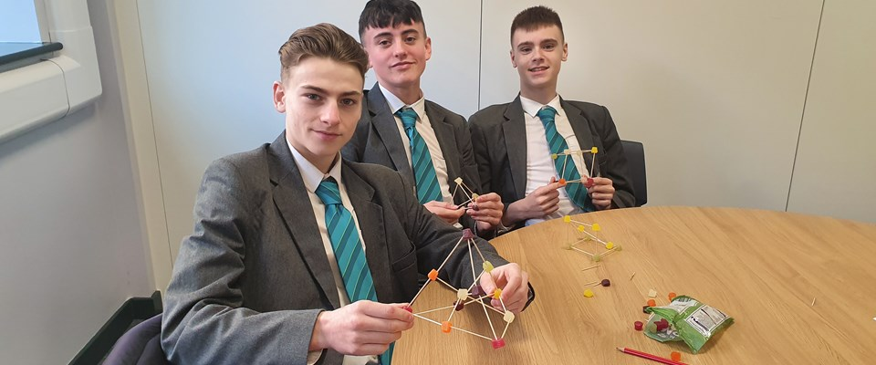 Three students hold a Maths puzzle made from cocktail sticks and sweets.